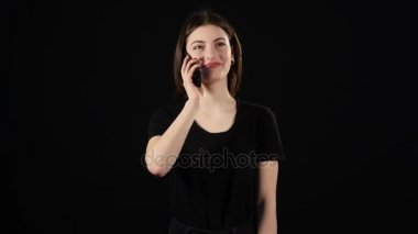 Beautiful happy young woman talking on mobile phone isolated over black