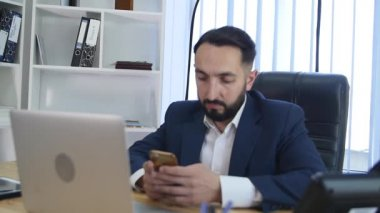 Manager of the company texting in the office