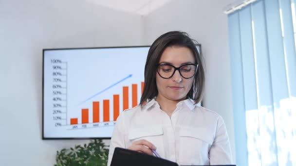 Šťastná žena manažerka v moderní kancelářské interiéru, mladá chytrá sekretářka usmívající se pro někoho během práce na přenosné digitální tablet