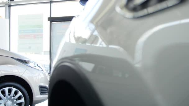 mladá rodina přichází do autodům výběru vozu, aby si ji koupili