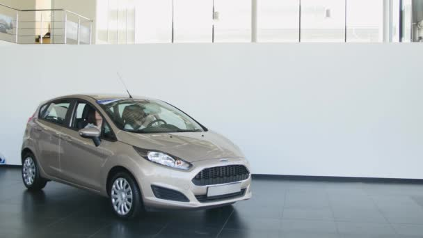 young family chooses a new car in the showroom, car buying and success concept, sitting in the car