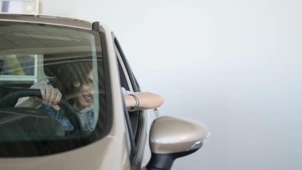 Donna felice che mostra la chiave della sua auto nuova. Business auto, vendita auto, concetto di tecnologia e persone - maschio felice con un rivenditore di auto in auto show o salone