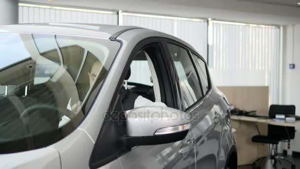 Uomo felice che mostra la chiave della sua auto nuova. Business auto, vendita auto, concetto di tecnologia e persone - maschio felice con un rivenditore di auto in auto show o salone. Giovane con un commesso in un salone