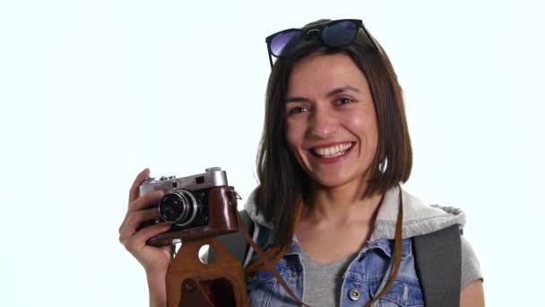 hübsche junge Fotografin mit alter Vintage-Kamera beim Fotografieren, Studioaufnahme auf weißem Hintergrund. schöne fröhliche Mädchen mit Vintage-Fotokamera