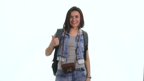 Attractive tourist girl with dark hair and wearing backpack isolating white background