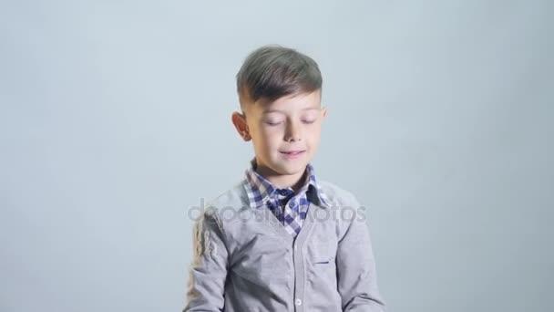 Junge wirft eine Mütze isoliert auf weißem Hintergrund