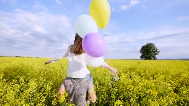 Girl with balloons on the shoulders of the guy runing in field rape