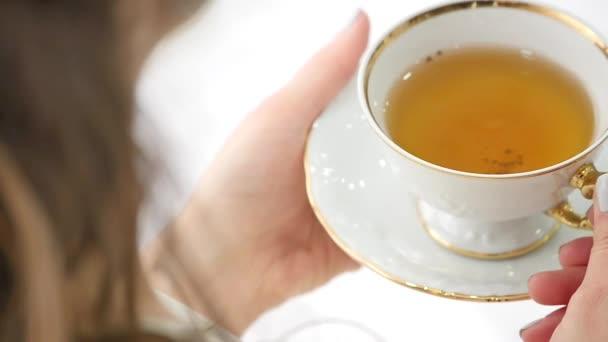 Ženské ruce hrnek horké čaje ráno. Dobré ráno čaj nebo koncept zprávy šťastný den