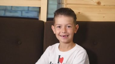 Portrait of funny little boy in cafe