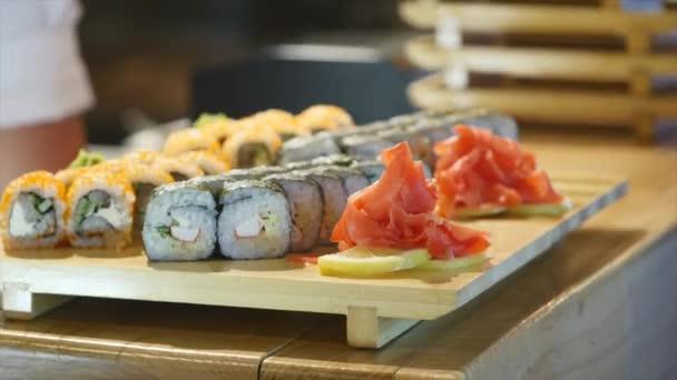 Cook hozza lemezek sushi tekercs a tábla és a pincér veszi őket. Roll Philadelphia az egyik legtöbb népszerű áll feltétlenül krémsajt, és a tetejére vékony szelet lazac csomagolva