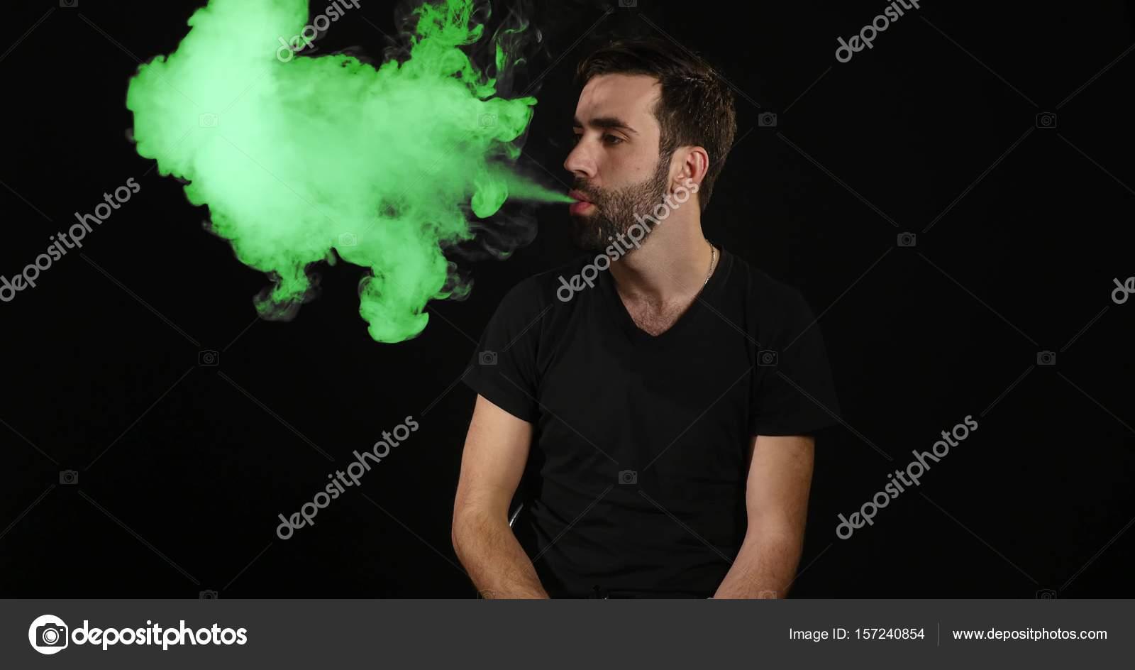 joven vaping con un cigarrillo electrónico y hace unas nubes de humo ...