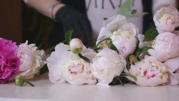Munkahelyi virágüzlet: nő, ami a csokor fehér rózsát és a különböző virágok. Virágüzlet. Virágbolt. Csokrok kidolgozása. A folyamat létrehozása virág kompozíció. Virág kompozíció