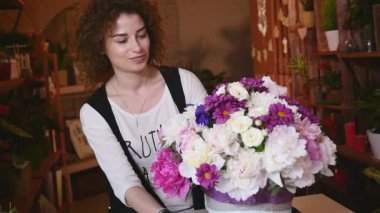 Young woman working as florist in flower shop and looking at camera, smiling with bouquet on desk