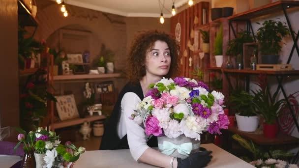 mladá žena pracuje jako květinářka v květinářství a při pohledu na fotoaparát, usmívá se kytici na stůl