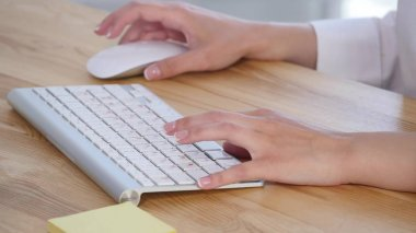 Young womans hands typing at computer keyboard