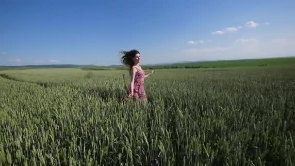 Beauty girl running on green wheat field. Freedom concept. Happy woman outdoors. slow motion