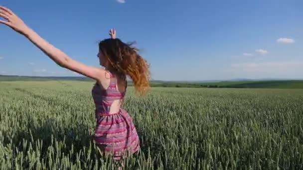 schöne junge Frau springt auf grünem Weizenfeld