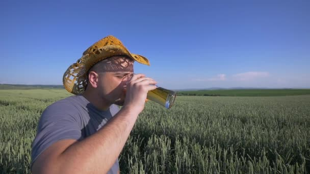 people, drinks and alcohol concept - close up of young man drinking beer from glass over cereal field background