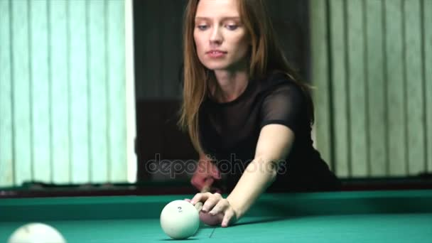 Young woman playing billiard game