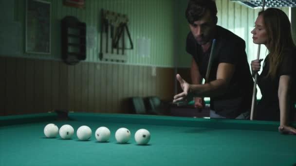Mann zeigt Mädchen, wo man den Ball schlägt - junge Frau erhält Rat, wie man beim Billardspielen Billardball schießt