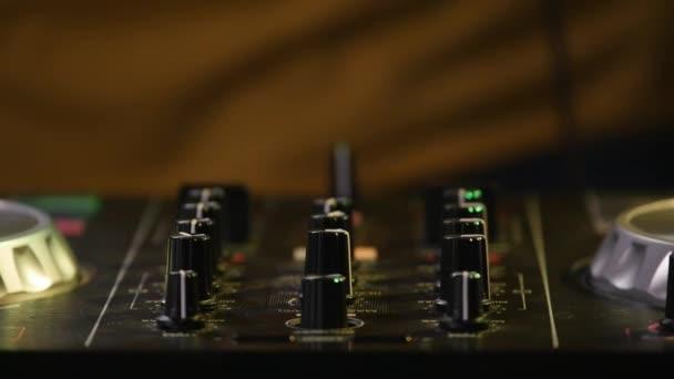 DJ mixes songs on equipment, hands closeup