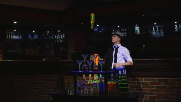 Acrobatic show performed by barman juggling bottle. bar background