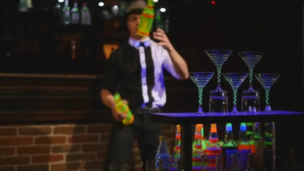 Acrobatic show performed by barman juggling two bottles. bar background. slow motion. selective focus