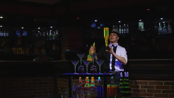 Acrobatic show performed by barman juggling two bottles. bar background. slow motion
