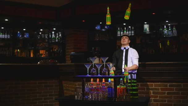 Acrobatic show performed by barman juggling four bottles. slow motion