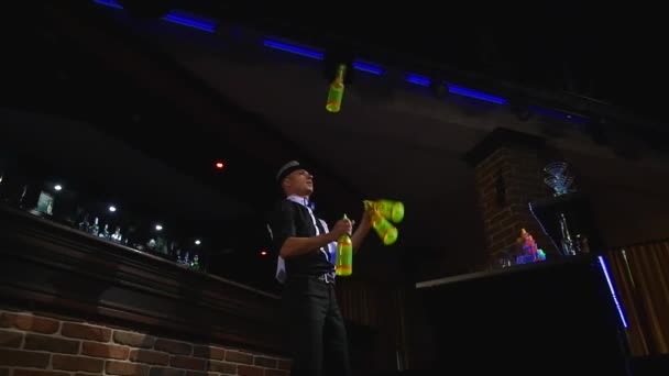 Acrobatic show performed by barman juggling four bottles. slow motion. bottom view