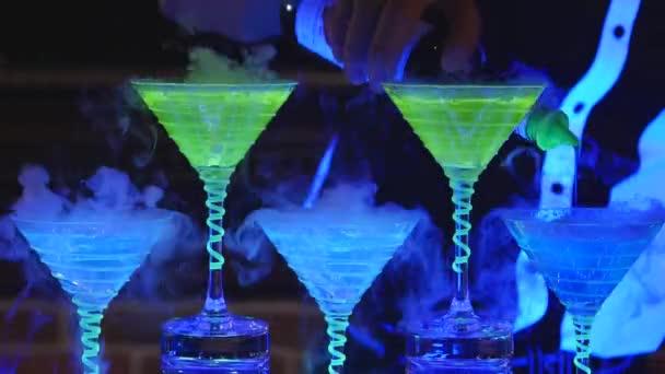 Barmann mit Eiswürfel-Cocktailglas. Barkeeper, der alkoholische Cocktails zubereitet. Nahaufnahme