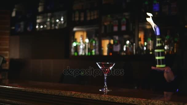 Junge, attraktive professionelle Barkeeper, Barkeeper machen coole, professionelle, erstaunliche Tricks mit zwei Flaschen am Ellenbogen, fangen, werfen, Feuershow hinter der Bar,