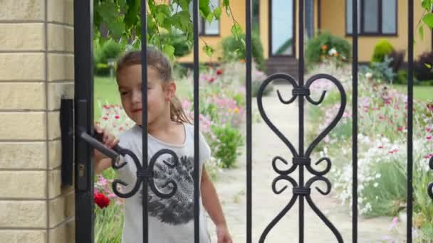 Little girl coming home, opening, closing gate, yard, summer