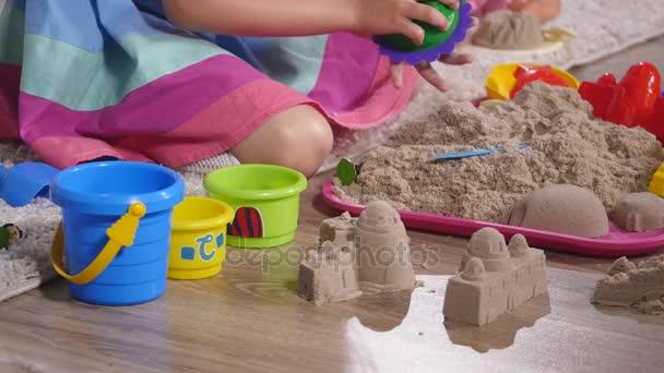 Ruční roztomilá malá blondýnka hraje písku ve studiu. Detailní záběr