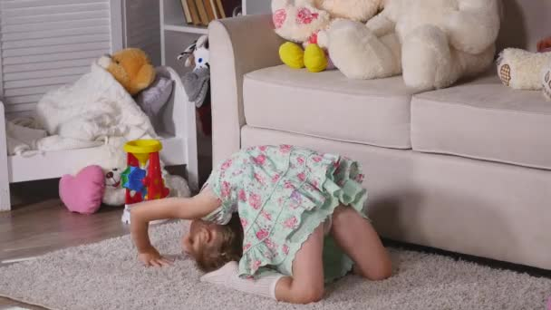 A little girl, adorable young talented dancer does ballet poses and stretching exercises on the floor at home