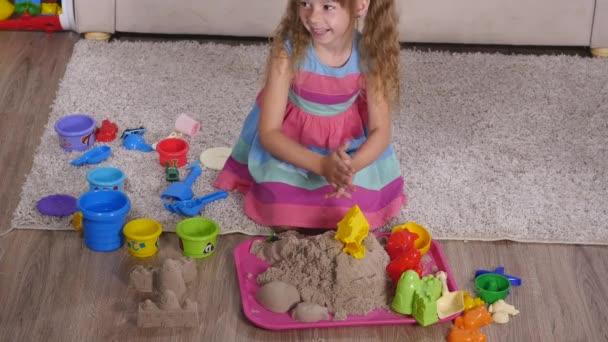 Roztomilá blondýnka hraje písek ve studiu. pohled shora