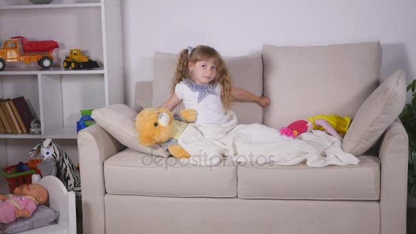 Dítě dívka se probudí z režimu spánku. Pěkný dítě dívka se těší Slunečné ráno. Dobré ráno doma