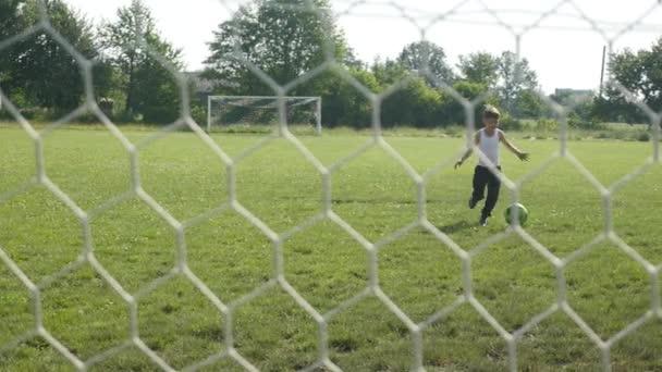 Kis fiú rugdossa a labdát, a cél