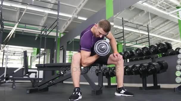Muži, kteří pracují rukama v tělocvičně, že zvedání činky a práci jeho biceps