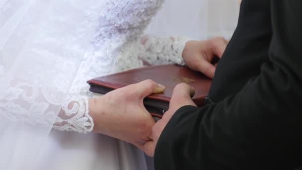Nevěsta a ženich ruce Bibli. Ženich a nevěsta místo rukou na Bibli k výměně sliby
