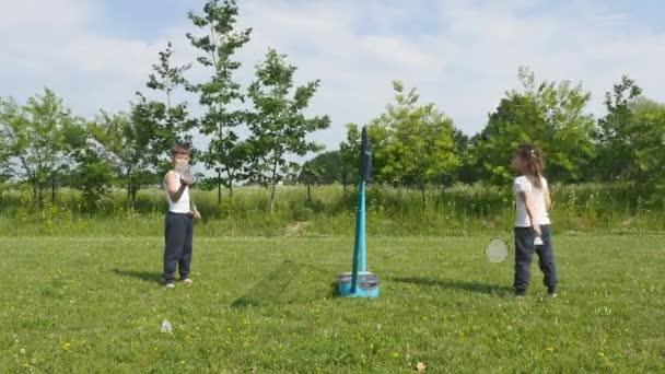 Mladý dospívající chlapec a dívka hrát badminton v louce s lesem v pozadí. Děti s badmintonové rakety v rukou. Přátelé mají zábavu v letním parku na den