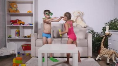 Two happy kids in swimsuits. Boy in diving mask and The girl is blowing bubbles in room