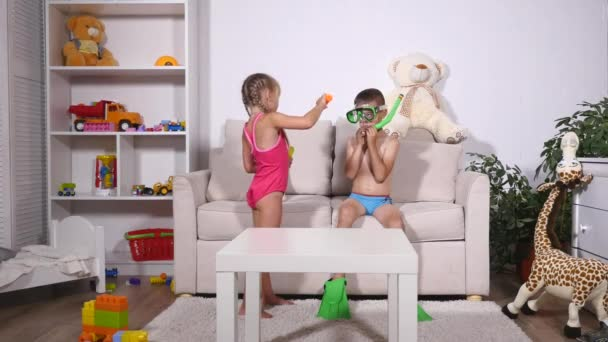 Two happy kids in diving mask sitting together in sofa