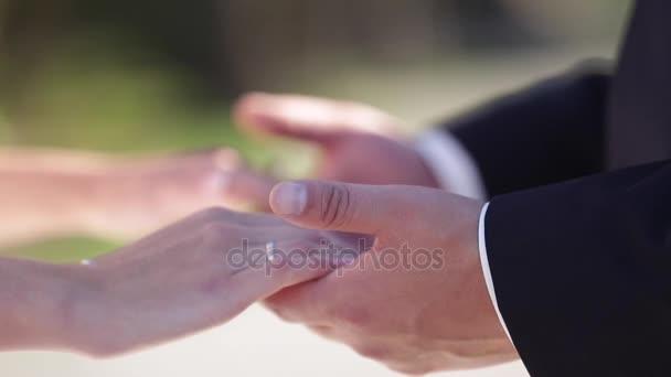 mani di un eterosessuale di nozze coppia con fedi nuziali sulle dita. Sposa e sposo. Coppie nellamore che tengono le mani. coppia appena sposata. uomo felice e donna nellamore. nuova famiglia. vivere felici e contenti
