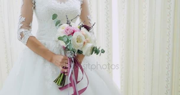 Wunderschönen Brautstrauß in Händen der jungen Braut gekleidet in weißen Brautkleid. Nahaufnahme des großen Haufen von frischen weißen Rosen in weiblichen Händen. Anonyme Braut halten Blumen