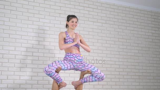 Akrobatická jóga. Mladá žena a muž provádění cvičení. Kombinace akrobacie a jóga
