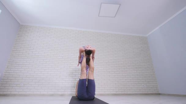 Mladá žena a muž cvičení akrobatická jóga. Kombinace akrobacie a jóga. 4k
