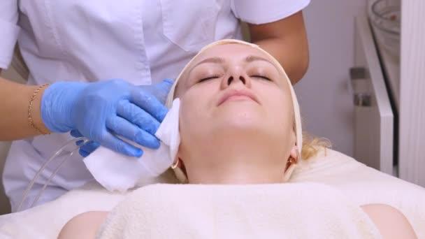 Žena leží na gauči během kosmetické procedury. Profesionální kosmetička dělá obličeje, masáže ve spa salonu. Péče o obličej. Krása, zdravé a koncepce mládeže