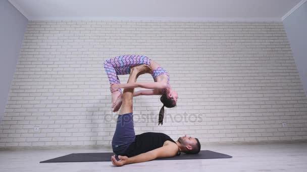 Gyönyörű pár acro jóga. Fiatal oktatók jóga stúdióban. Két sikeres fiatalok végre acro jóga gyakorlatok