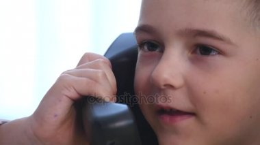 Little boy speaking on phone in the office. close up